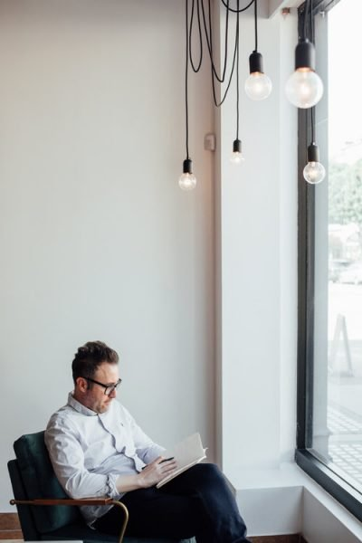 A senior copywriter creates content while sitting by window