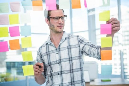 A writer using Post-it notes to brainstorm and organize ideas